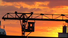 The Silhouette Of A Construction Crane Against The Orange Sky During Sunset
