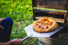 High Angle Shot Of A Male Taking Ready Pizza Out Of Oven Outdoors