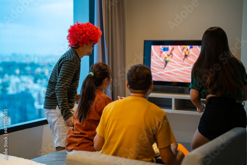 Fototapeta premium Group of Asian people friends sit on sofa watching and cheering sports games competition on TV together at home. Excited man and woman sport fans celebrate sport team victory in national sports match