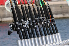 Fishing Rods In Holders On Fishing Charter Boat Parked At Harbour On Bright Sunny Day