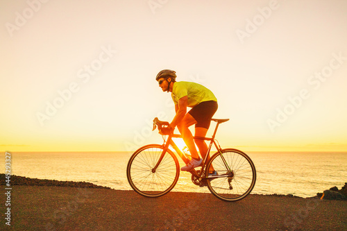 Fototapeta Triathlon competition man cyclist triathlete riding road bike cycling uphill in difficult race during sunset on ocean coast landscape
