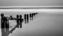 Grayscale Shot Of A Calm Sea With Wooden Wave Breaker Under A Cloudy Sky