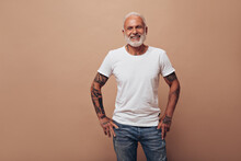Adult Man With Tattoos Poses On Beige Background. Handsome Guy With Gray Beard In White T-shirt And Blue Modern Jeans Smiles