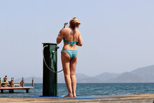 Shower On A Beach, Woman In Striped Swimsuit Washes Standing On Background Of Sea And Misty Mountains. Hot Weather, Summer Resort And Vacation