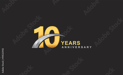 Fotografering 10th years anniversary logo with golden ring and silver swoosh isolated on black background, for birthday and anniversary celebration
