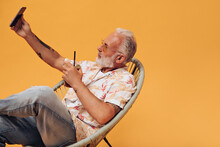 Cool Man In Stylish Shirt Holding Cocktail And Taking Selfie On Orange Background. Handsome Adult Guy In Tattoos Makes Photo In Summer Shirt