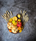 Fototapeta Kawa jest smaczna - Wiccan Altar for Lammas, Lughnasadh pagan holiday. ears of wheat, homemade bread, flowers, apple, candle on dark background. symbol of celtic wiccan sabbath, summer season. flat lay