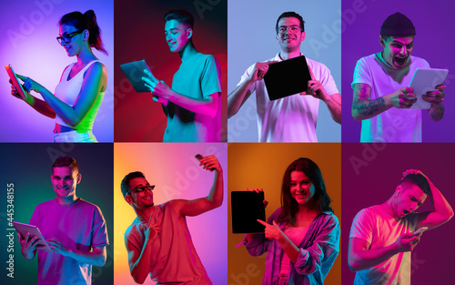 Fotografie, Obraz Group of young girls and boys with digital devices isolated on colored background in neon light