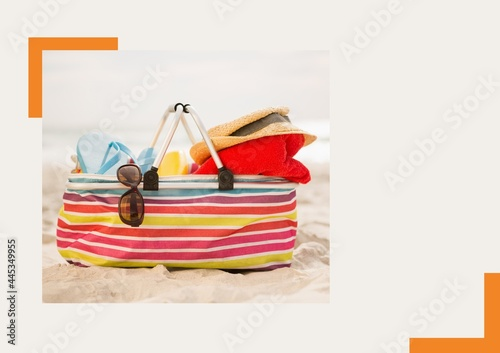 Photograph of bag with accessories at the beach against grey background