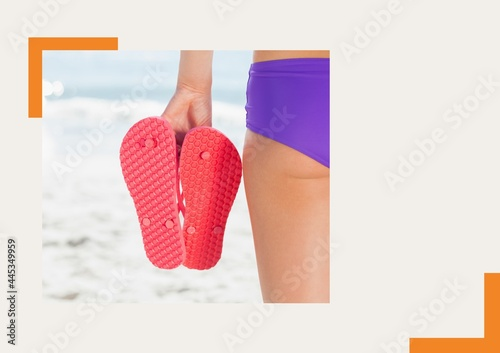 Photograph of mid section of woman holding flip flops at the beach against grey background