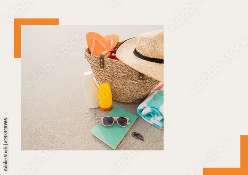 Photograph of basket with accessories at the beach against grey background