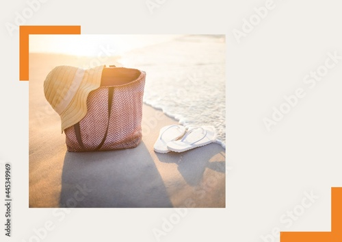 Photograph of hat over a bag and flip flops at the beach against grey background