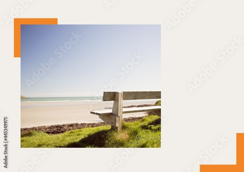Photograph of a bench at the beach against grey background