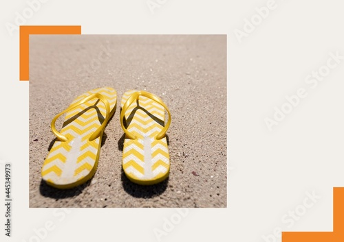 Photograph of yellow flip flops at the beach against grey background
