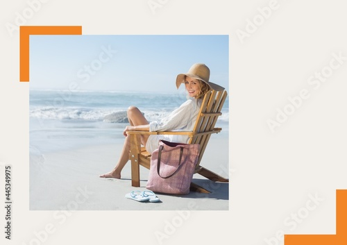 Photograph of caucasian woman sitting on a chair smiling at the beach against grey background