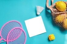 Beach Leisure Flat Lay Composition Photography. Pink Badminton Rackets, Bag With Lemons, Rubber Duck And Empty White Paper Sheet On A Blue Background. Summer Holidays Concept Mockup