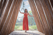A Beautiful Woman In An Orange Dress Poses In A Bamboo Arch