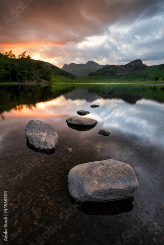 Dramatic sunset reflections in lake with mountains. Rocks in foreground. Rugged British landscape in rural open countryside. Blea Tarn, Lake District, UK.