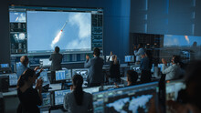 Group Of People In Mission Control Center Witness Successful Space Rocket Launch. Flight Control Employees Sit In Front Computer Displays And Monitor The Crewed Mission. Team Stand Up And Clap Hands.