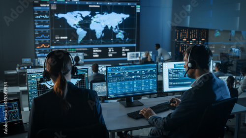 Shot of Officers in a Surveillance Control Center with Police Global Map Tracking on a Big Digital Screen. Monitoring Room Employees Sit in Front of Computer Displays and Analyze Big Data.