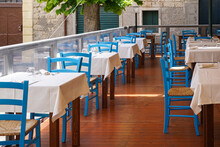 Empty Tables And Blue Chairs In Outdoor Restaurant
