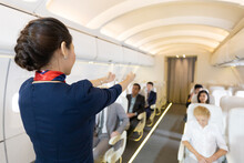 Back View Flight Attendant Giving Instructions Or Demonstrating About The Use Of Doors And Operations In Airplane