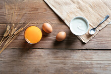 Bakery Ingredients, Table Background, Wood Planks – Raw Wheat Ears, Grain Seeds Sprinkled And In Terracotta Bowl, Eggs, Yolk In Glass Bowl On Table Mat, Mug Of Milk, Whisk – Close-Up Macro, Top View