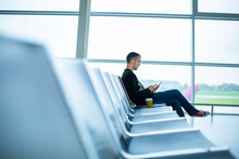 A Guy Is Sitting On An Empty Row Of Seats In Front Of A Large Stained Glass Window In An Airport Terminal, Waiting For A Flight