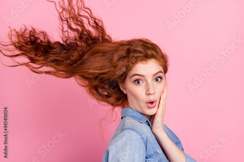 Fototapeta Photo of impressed funny young woman wear denim shirt arm cheek wind blowing iso
