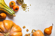 Autumnal Background With Pumpkins, Pears, Walnuts, Pumpkin Seeds, Persimmons And Copy Space