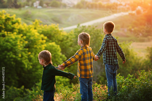 Tableau sur Toile Group of happy children playing on meadow, sunset, summertime