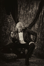 Stylized, Antiqued Portrait Of Victorian Steampunk, Sitting With Hand On Knee And Holding Pipe, Looking Stern, Wearing Bowtie, Leather Tail Coat And Sitting On Trunk.