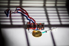 Champion Gold Medal, Doping Substance Syringe, Pill Tablet And Prohibited Substance Vial With Lights And Shadows Of A Curtain Entering Through The Window. Sport And Doping Concept