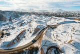 Aerial view of highway stretching through snow-covered terrain in Cappadocia