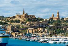 Yachts Moored In Sea By Ghajnsielem Parish Church In City On Sunny Day Gozo, Malta
