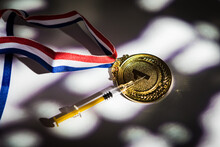 Champion's Gold Medal And Syringe With Doping Substance With Lights And Shadows Coming Through The Window. Sport And Doping Concept