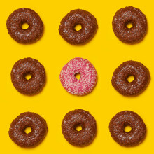 Pattern Of Brown Doughnuts With Single Pink One In Middle
