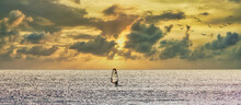 Windsurfer Furrowing A Silver Sea By The Reflections Of The Sun On A Cloudy Sunset