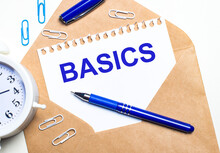 On A Light Background, A Craft Envelope, An Alarm Clock, Paper Clips, A Blue Pen And A Sheet Of Paper With The Text BASICS.