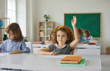 Elementary School Student Raises Her Hand, Ready To Answer The Teacher's Questions In Class. Smart Little Curly Girl Is Sitting At A Desk Next To Her Classmate In The Classroom. Concept Of Education.
