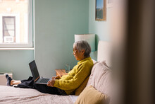 Senior Woman Using Laptop While Sitting In Bedroom At Home