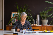 Senior Woman Reading Newspaper While Sitting At Table With Coffee