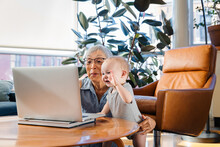 Senior Woman Sitting With Granddaughter Using Laptop To Video Call