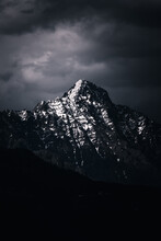 Vertical Shot Of Rocky Mountains Covered In The Snow Under A Dark Cloudy Sky