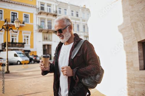 Slika na platnu Positive man poses outside and holds coffee cup
