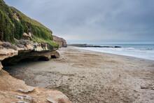 Playa Junto A Rocas Cubiertas De Vegetacion.