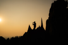 Silhouette Of Young Asian Man Standing On Beautiful Sharp Shape Limestone Mountains Holding Cellphone Taking A Picture Of Landscape In Front Of Him With Orange Sky In Background On Sunset Or Sunrise.