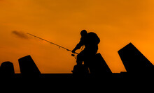 Silhouette Of A Man Wiht A Backpack Fishing Under An Orange Sky At Sunset