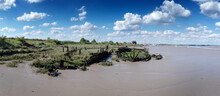 An Abandoned Boat Decaying On The Mud Banks