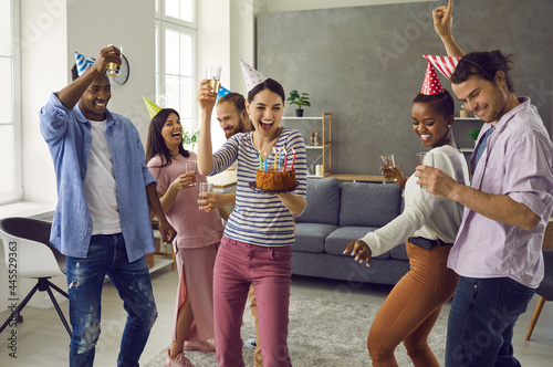 Fotografie, Tablou Diverse multiracial group of happy people in funny hats dancing and having fun at casual birthday party at home